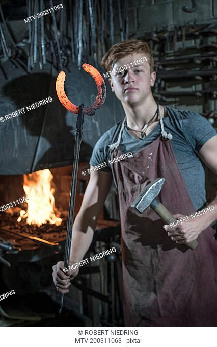 Apprentice blacksmith with hammered red hot horseshoe at workshop