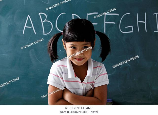 young girl with pony tails smiling in front of chalk board