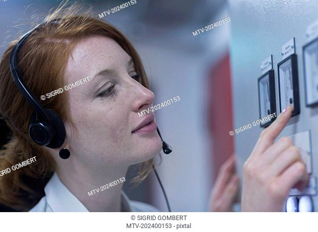 Young female engineer wearing headset and examining in control room, Freiburg im Breisgau, Baden-Württemberg, Germany