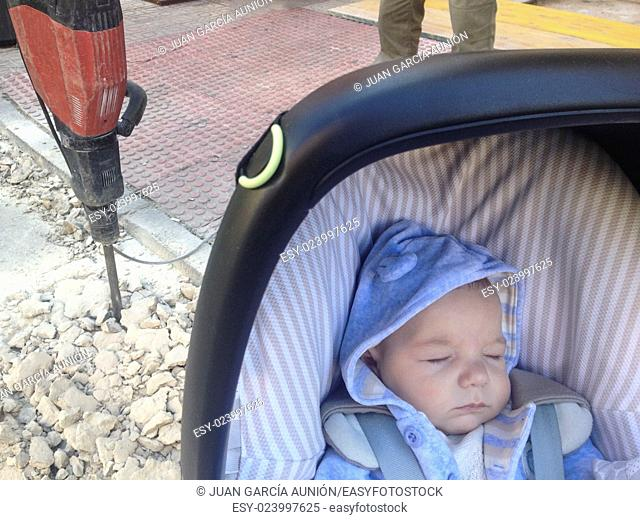 Sleeping four month baby boy lying in strolller getting close dangerously to jackhammer on the street