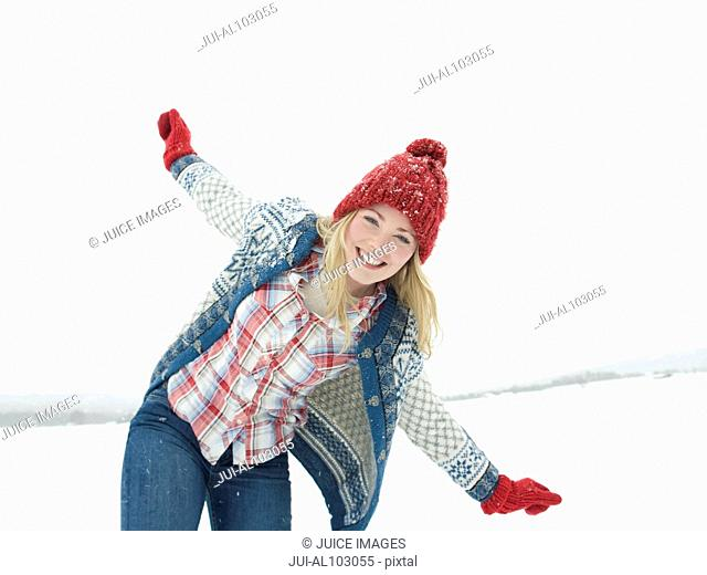 A young woman wearing a red woolen hat and gloves playing in the snow