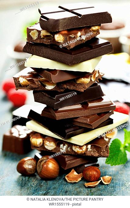 An assortment of white, dark, and milk chocolate with nuts on wooden background