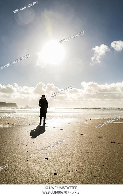 France, Bretagne, Finistere, Crozon peninsula, woman standing on the beach