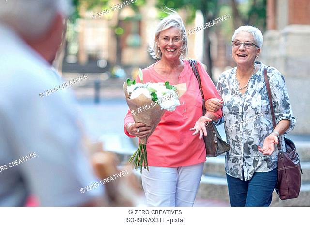 Two mature women carrying bouquet arm in arm in city
