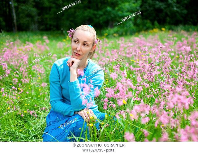 happy young woman in the field of wild flowers
