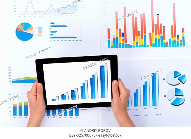 Close-up Of Person Analyzing Financial Graph Diagram On Digital Tablet