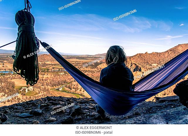 Rock climber on hammock on summit, Smith Rock State Park, Oregon, USA