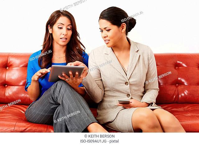 Two businesswomen having meeting, looking at digital tablet