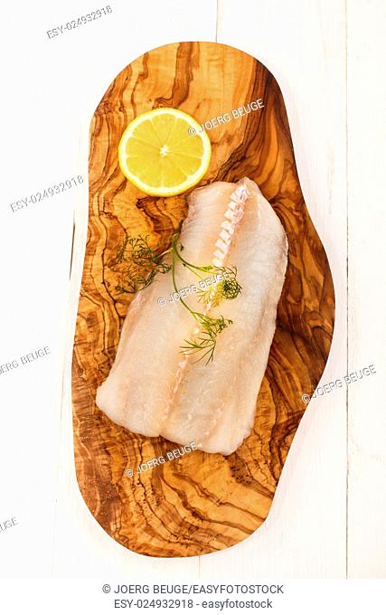 raw haddock with dill and slice lemon on a wooden board