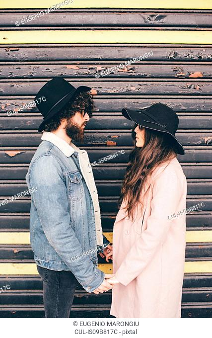 Portrait of young man and woman, face to face, holding hands, pensive expressions
