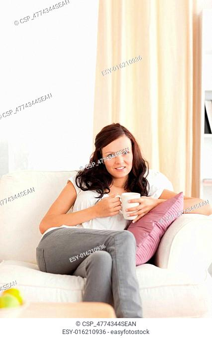 Woman holding a cup looking into the camera