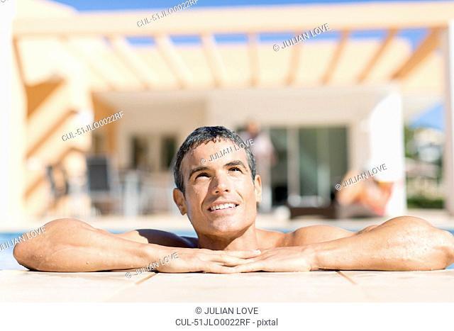 Man resting on edge of swimming pool