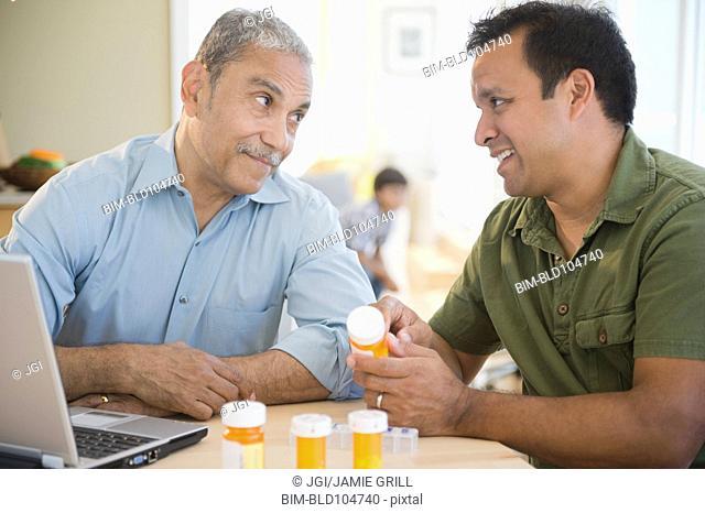 Hispanic son explaining medication to father