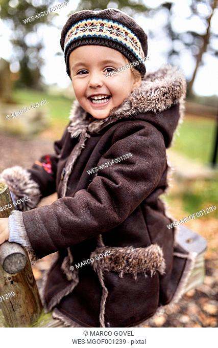 Portrait of happy little girl on a playground in autumn