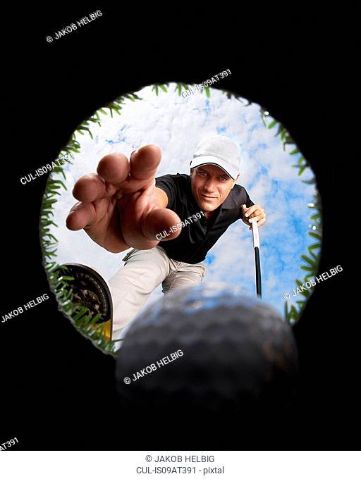 View through hole of golfer reaching for golf ball