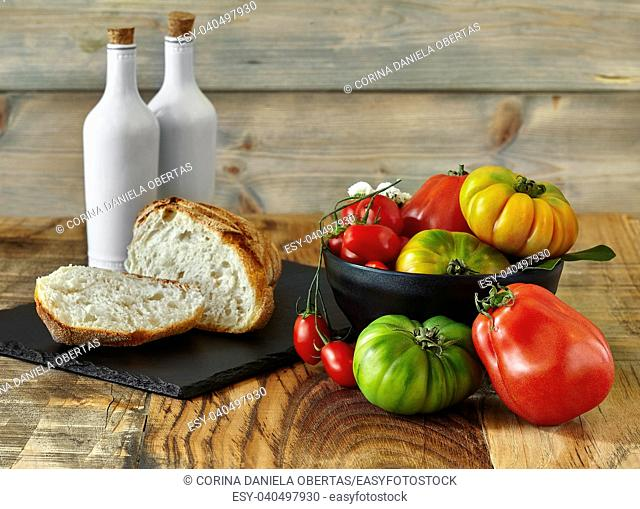 Fresh yellow, red and green tomatoes inside black bowl with bread, oil and vinegar on slate and wood background