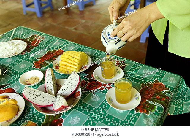 Vietnam, Mekong-Delta, woman, detail, hands, tea, pours, plates, fruits, Asia, cut open southeast-Asia, people tradition tea-rite tea-pot tea-glasses, pours out