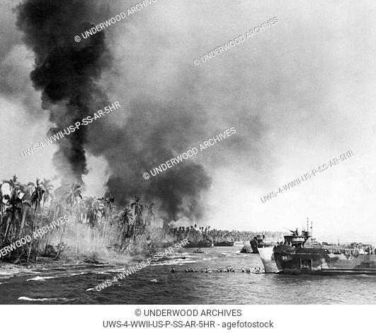 Leyte Island, Phillipines: November 1, 1944 U.S. troops wade ashore from their amphibious craft onto a still smoldering beach from the pre-invasion bombardment