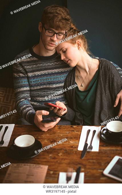 Couple embracing and using mobile phones in the cafe
