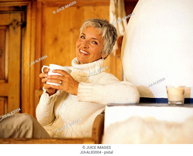 Senior woman smiling with coffee in chalet