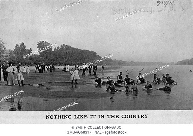 A postcard from a photograph of people on the beach and in the water, the people on the beach are mostly wearing formal clothing while those in the water are...