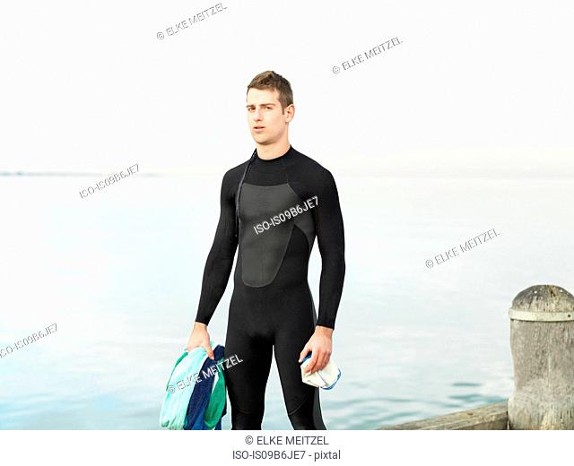 Man by sea wearing wet suit looking away, Melbourne, Victoria, Australia, Oceania