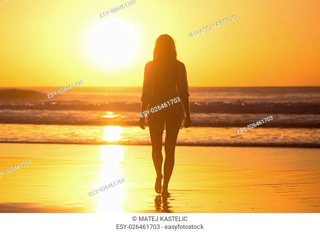 Woman walking on sandy beach in sunset leaving footprints in the sand. Beach, travel, concept. Copy space. Vertical composition