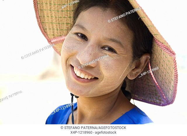 Portrait of a young Burmese woman in Mingun with thanakha paste on her face. Thanakha paste is made from the soft bark of the thanakha tree and is used as...