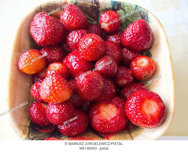 Large bowl of fresh strawberries with bract leaves
