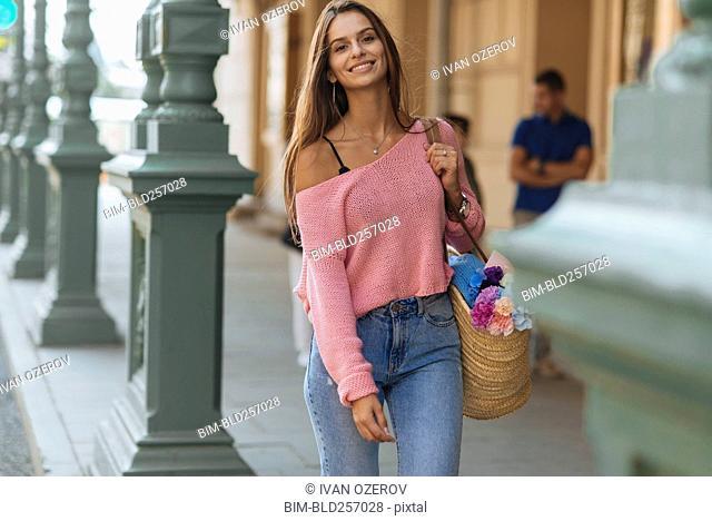 Smiling Caucasian woman carrying flowers on sidewalk