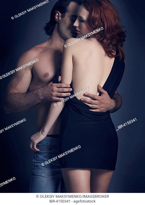 Young sexy couple, man with bare torso embracing woman in backless dress