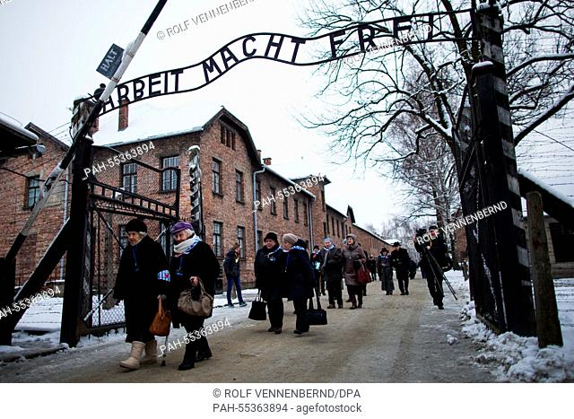 Survivors pass the main gate of the former Nazi-German concentration and extermination camp KL Auschwitz I prior to a ceremony marking the 70th anniversary of...