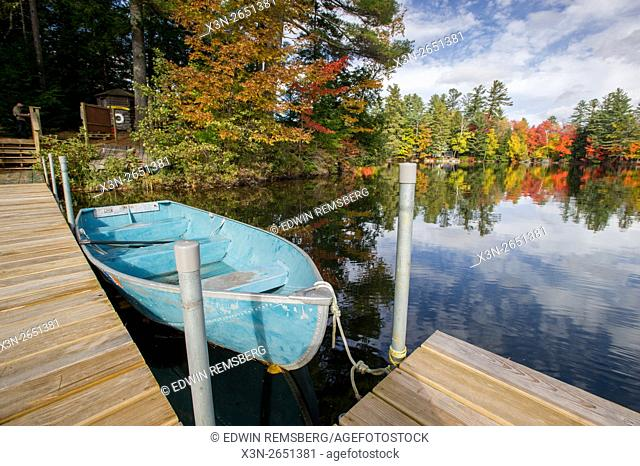 Rowboat next to a dock on with clouds and trees reflecting on the water during autumn in Maine