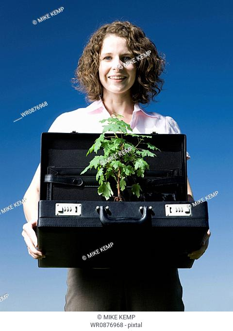 woman holding a briefcase with a tree in it