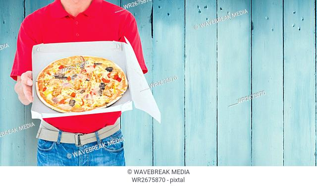 Delivery man holding pizza box against wooden background