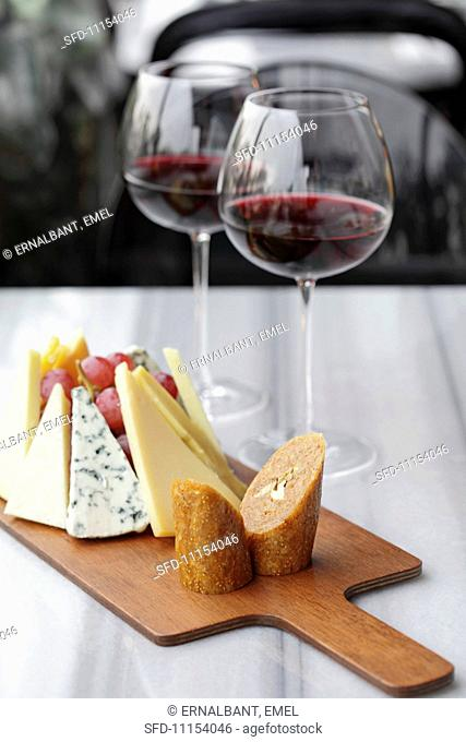 A cheeseboard with grapes and two glasses of red wine