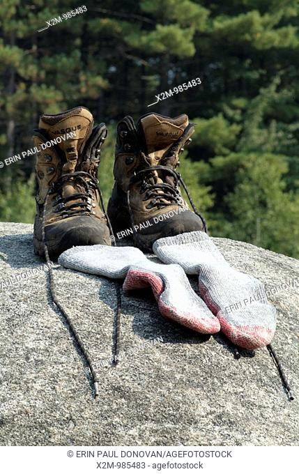 Hiking boots and socks on a large rock