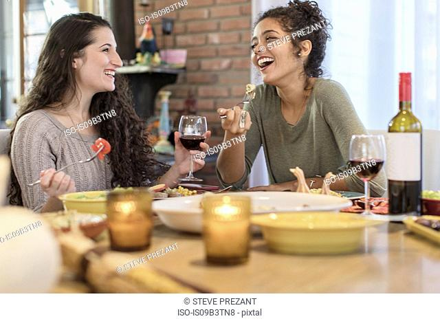 Two young women friends eating meal at kitchen table