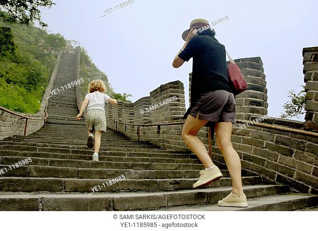 Mother and daughter climbing the steps on the Great Wall at Juyongguan Gate near Badaling, China