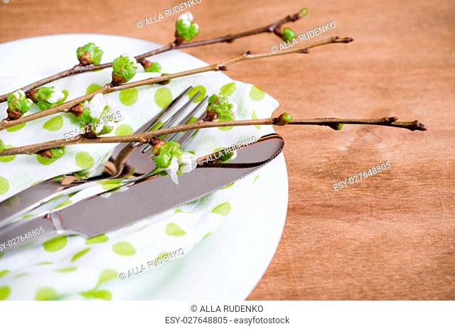Spring Festive Table Setting with Flowering Branch Cherries, Cutlery and Napkin on Wooden Rustic Table. Selective Focus