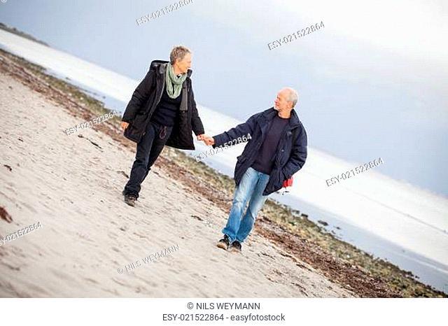 älteres glückliches paar macht einen strand spaziergang
