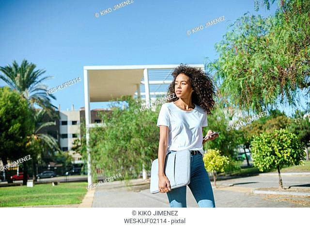 Portrait of young woman with mobile phone and laptop bag walking down the street looking at cell phone