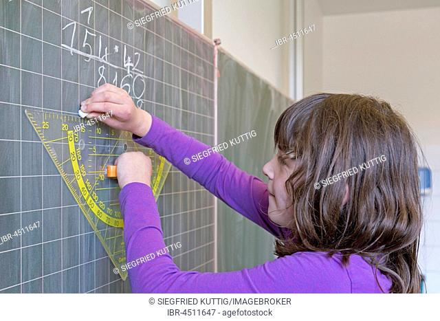 Student calculating on the blackboard, mathematics lesson, primary school, Lower Saxony, Germany