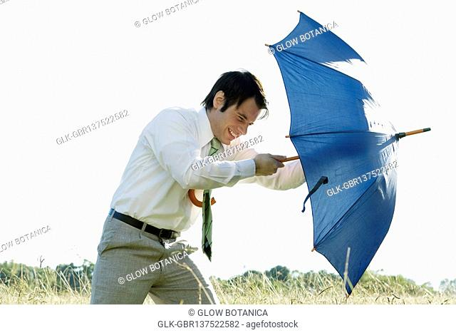 Businessman struggling with an umbrella
