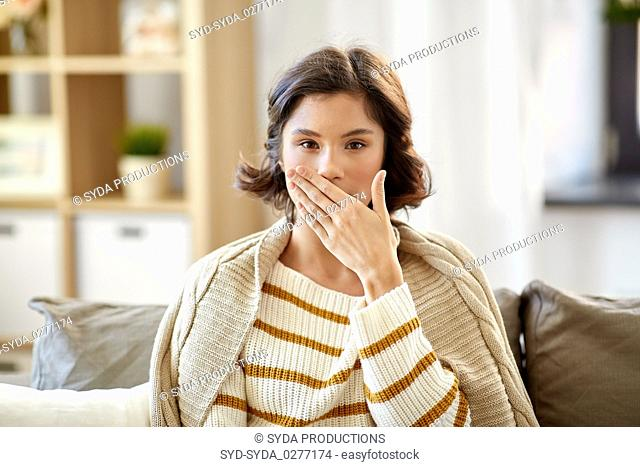 sick woman in blanket coughing at home