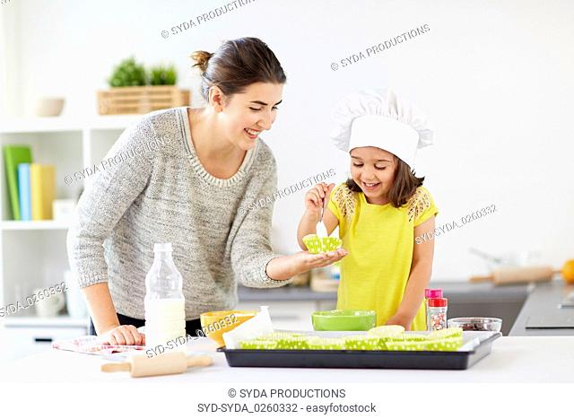 happy mother and daughter baking cupcakes at home