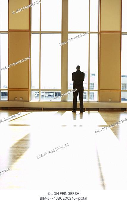 Businessman standing in sunlit room looking out window, North Bethesda, Maryland, United States