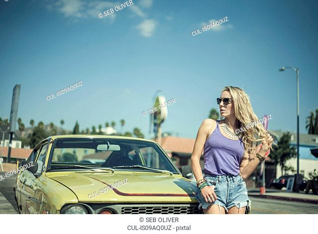 Young woman leaning against car