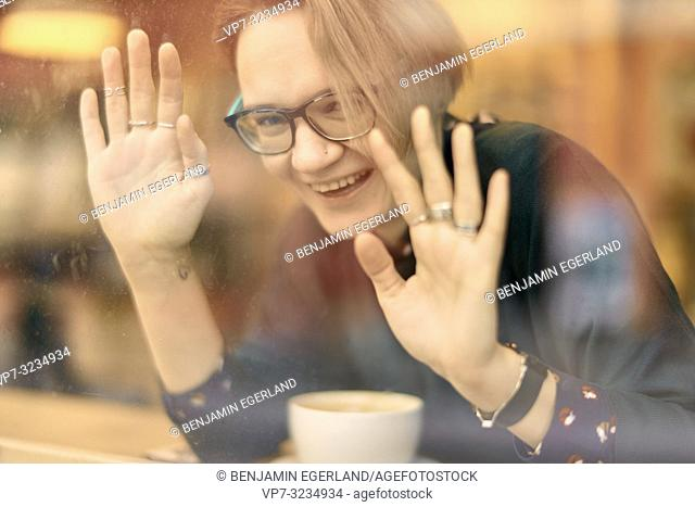 happy woman touching glass window, sitting indoors in café, taking a break, in Munich, Germany