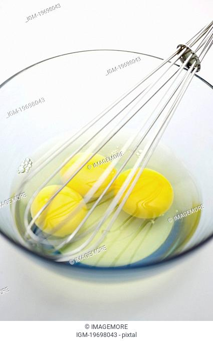 Egg yolks and egg wire whisk in bowl